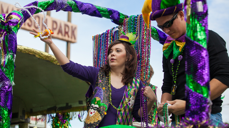 Float riders toss beads to the crowd at Shreveport's Krewe of Highland Mardi Gras parade.
