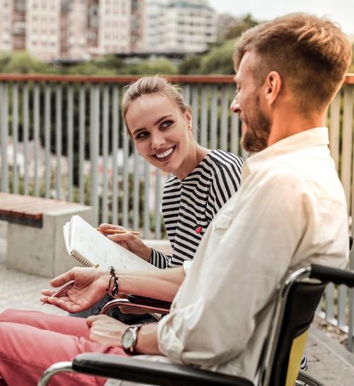 volwassen man in rolstoel met zijn assistente