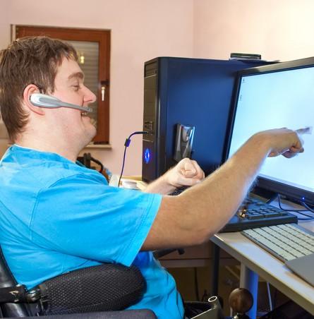 man in rolstoel met computer bezig