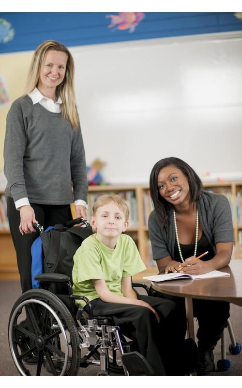 jongen in rolstoel met twee begeleiders