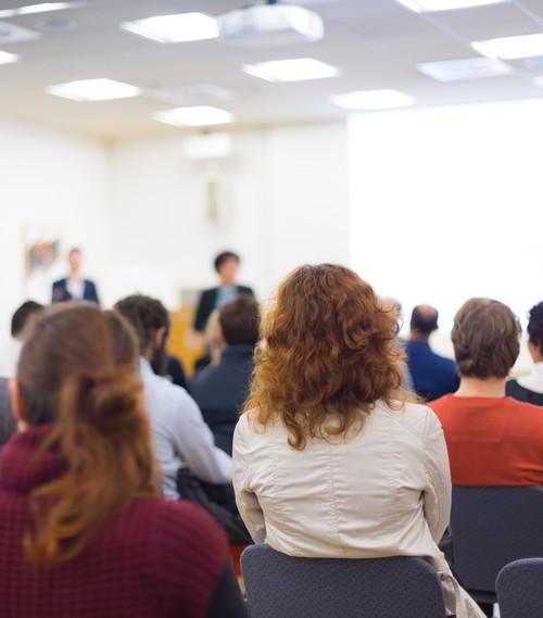 achterzijde van publiek op stoelen in conferentiezaal