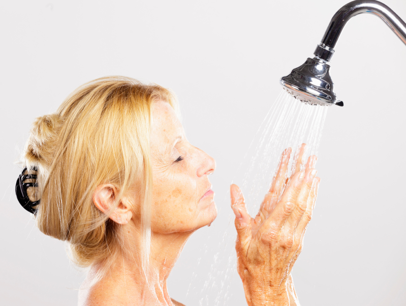 Image of a woman washing her face in the shower
