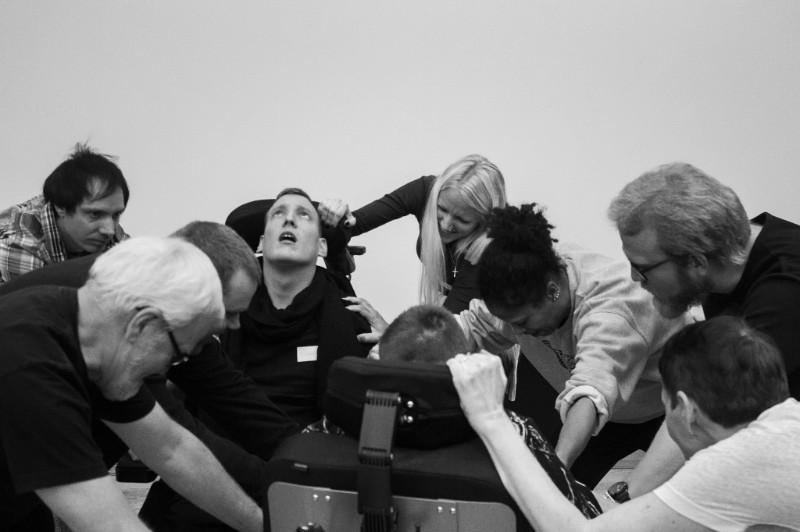 Syntolkning: Fotot är svartvitt, en grupp människor står i en klunga