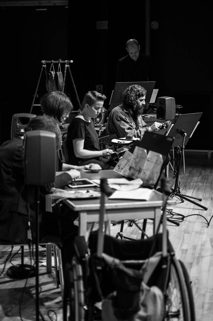 Syntolkning: Fotot är svartvitt, platsen är en scen. Bilden är tagen från sidan. Vi ser fem musiker, de fyra som är närmast spelar på ipads. Den femte tittar ner i sina noter. Bredvid honom hänger slagverk av olika slag.