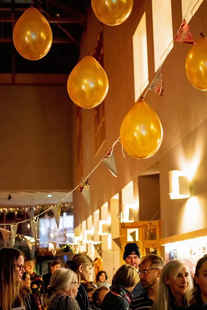 Syntolkning: I nedre femtedelen av bilden syns huvuden på ett flertal människor. Över dem hänger ballonger och vimplar i guld.