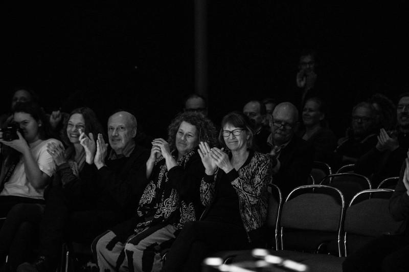 Syntolkning: Fotot är svartvitt. Bilden är tagen från scen på publiken, människorna där applåderar och ser glada ut.