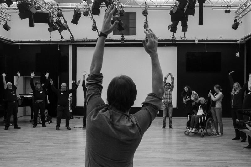 Syntolkning: Fotot är svartvitt, platsen en repetitionssal. Längst fram i bild ser vi ryggen av en person. Han sträcker upp sina armar i luften. På andra sidan rummet, vända mot os, ser vi en grupp människor som tolkar hans rörelse.