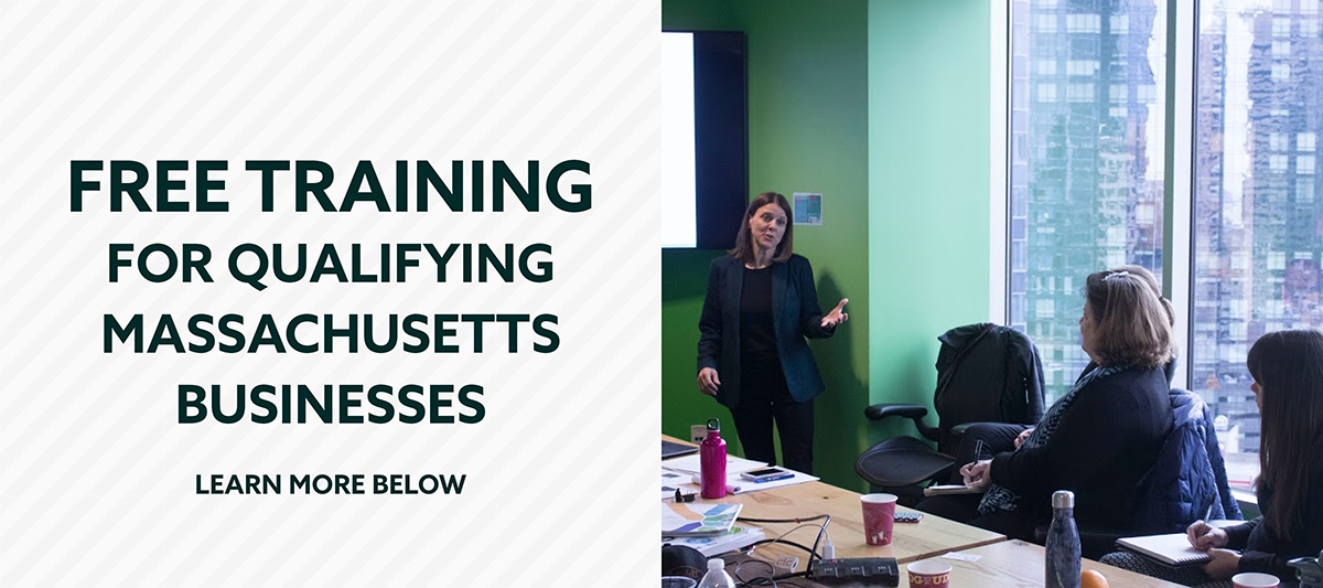Graphic: Free Training for Qualifying Massachusetts Businesses. Learn more below. Photo: A standing presenter hold out a hand talking in the direction of three attendees sitting at a conference table.