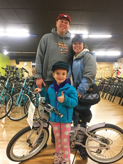 Charlotte Saven, winner of the 2017 SELCRA Daddy Daughter Dance bicycle drawing, picks up her prize at Hometown Bicycles with her parents