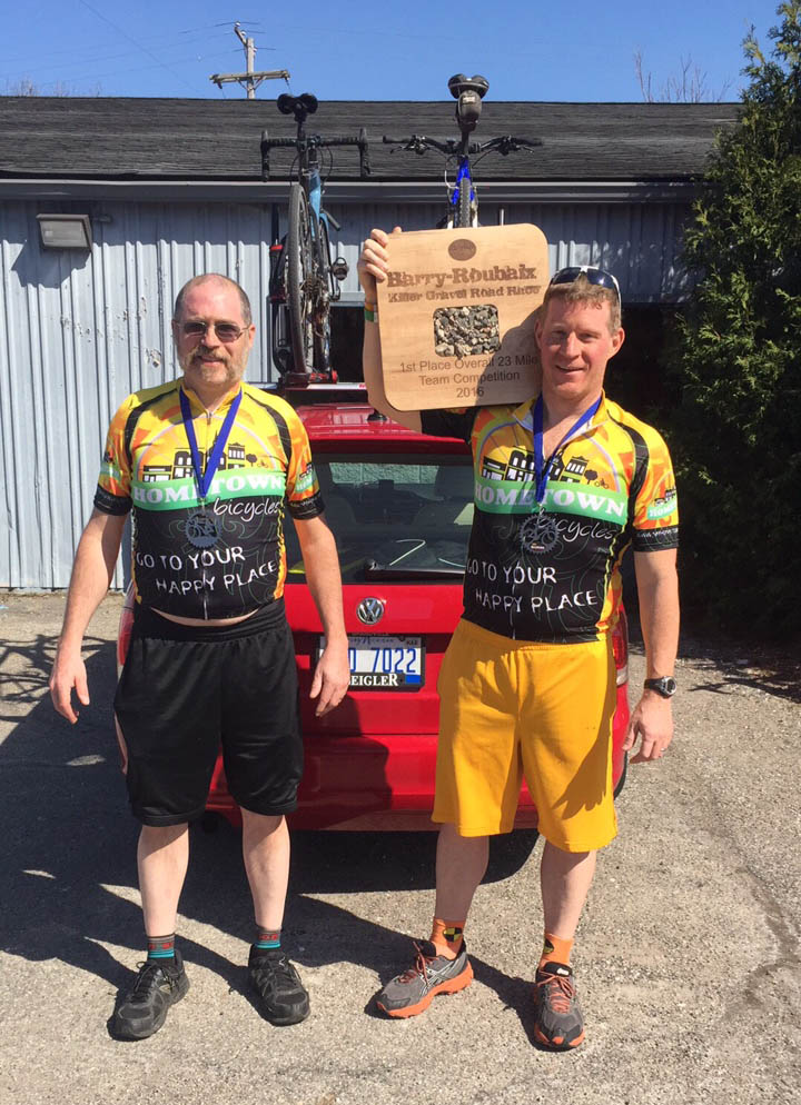 Team Hometown Bicycles Captain Jim Cleer holds aloft their 1st place Barry Roubaix trophy with Tom Hermann