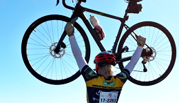 Hometown Bicycles Team rider raising bike over head at Tour de Livingston
