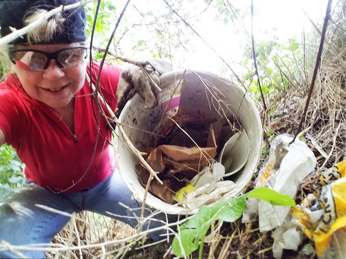 Hometown Bicycles Rides Coordinator Jean Steinberg clearing trash from Hometown's new trail