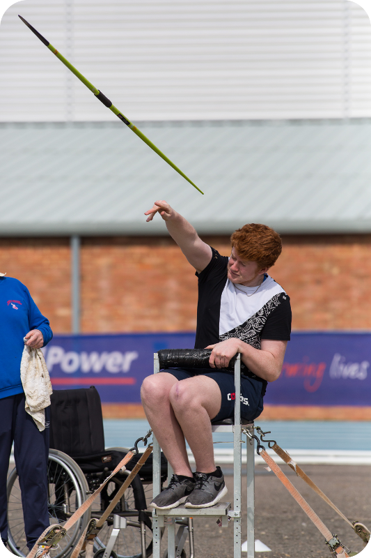 Young man throwing javelin from chair