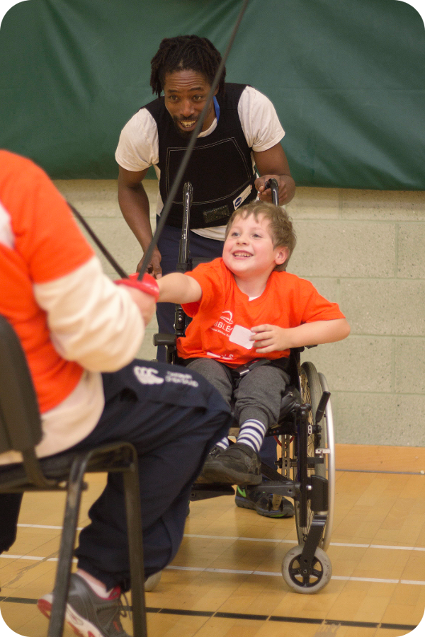 Boy in wheelchair taking part in fencing.