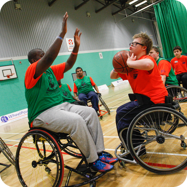 Boys in wheelchairs playing basketball