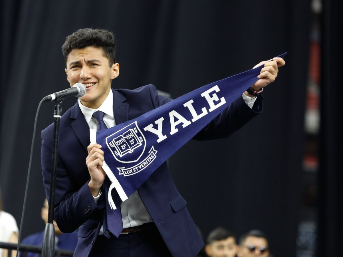 Senior holding Yale pennant on SSD stage