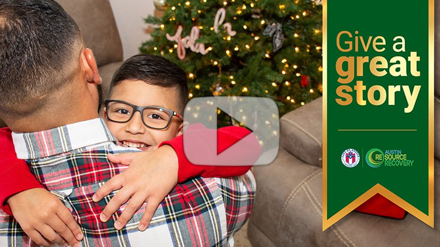 Father and son hug in front of Christmas tree, click to watch video