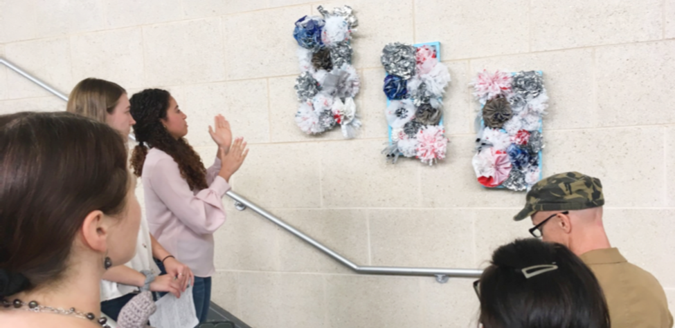 Students look at three pieces of three-dimensional floral art in a stairway.