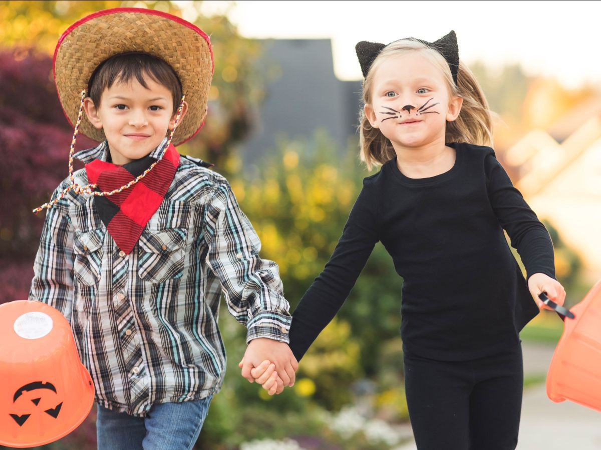 Kids dressed in homemade costumes: a cowboy and a cat