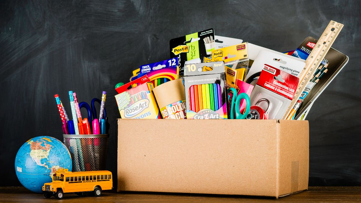 Box of school supplies including markers, scissors, crayons and a ruler.