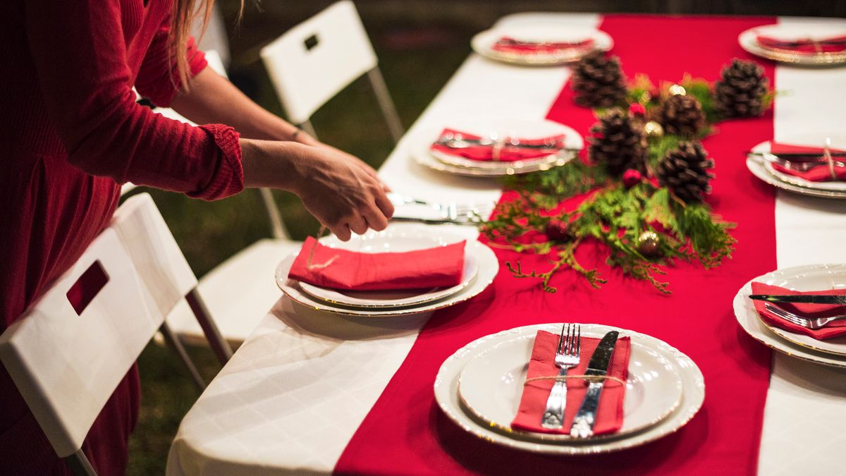 Woman sets table for a holiday meal.