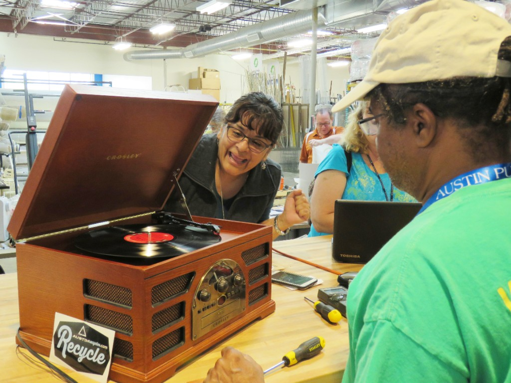 People fix a record player at a Fix-It Clinic.