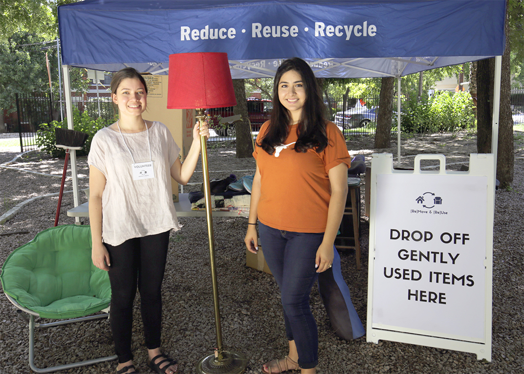 "Women at a drop-off center with a lamp and sign that says ""drop off gently-used items here."""