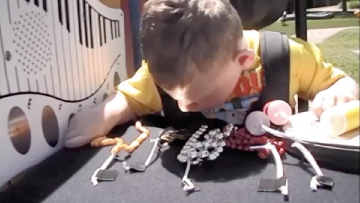 A boy in a wheechair interacting with an outdoor activity wall
