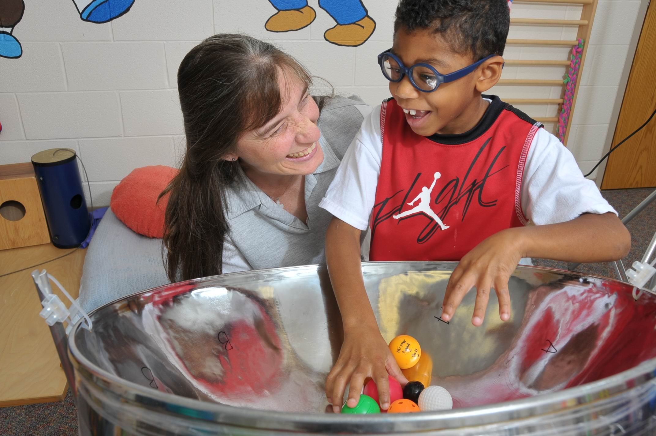 Boy with different types of balls on a steel drum