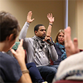 People raising hands during a workshop