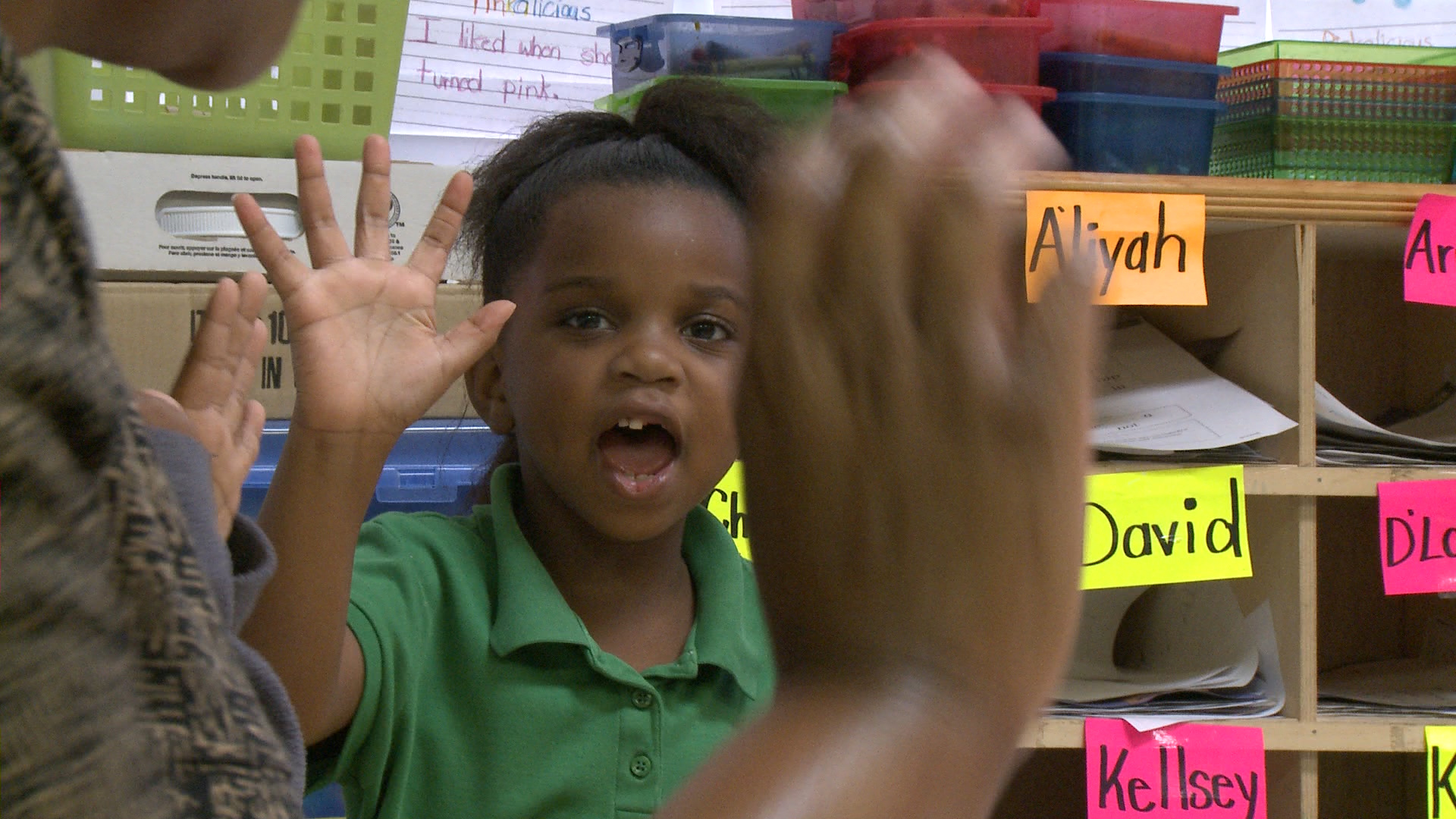 A young African American girl who is missing a tooth and raising her hand in class