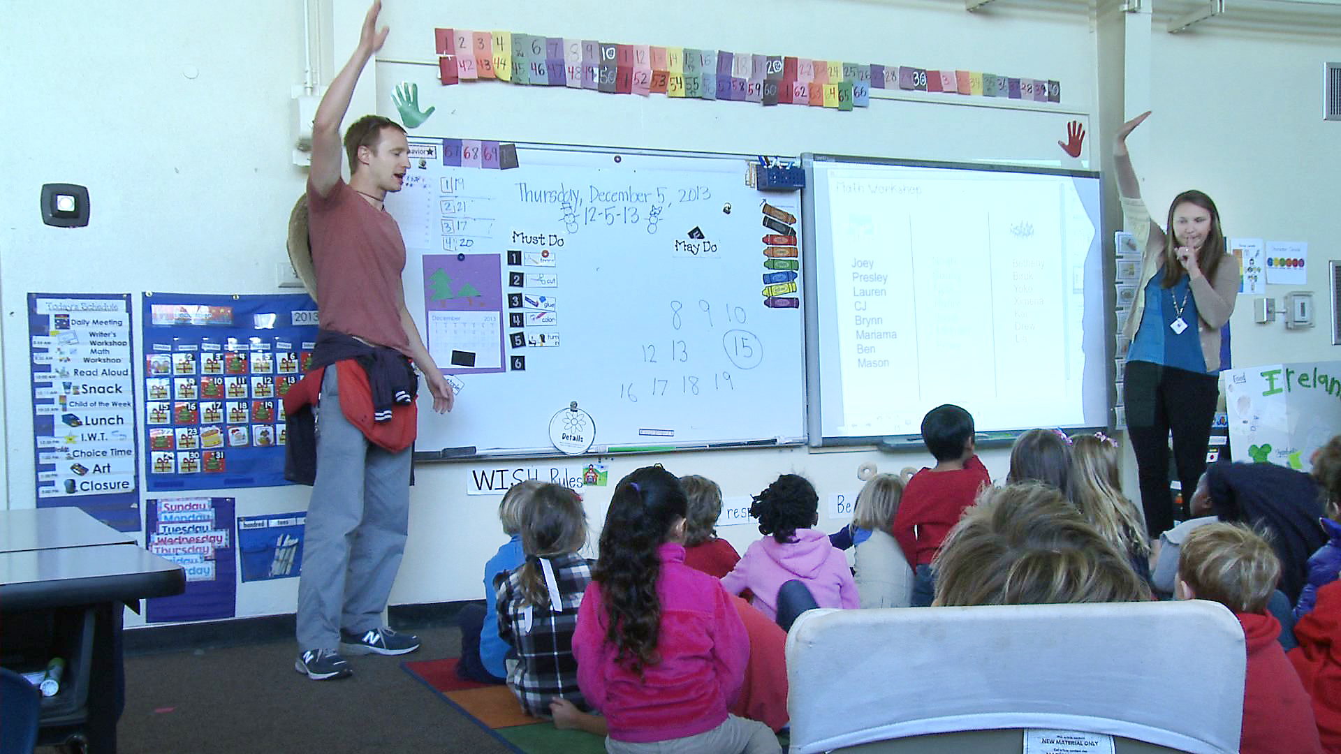 Students sitting in front of a white board and two teachers each raising a hand