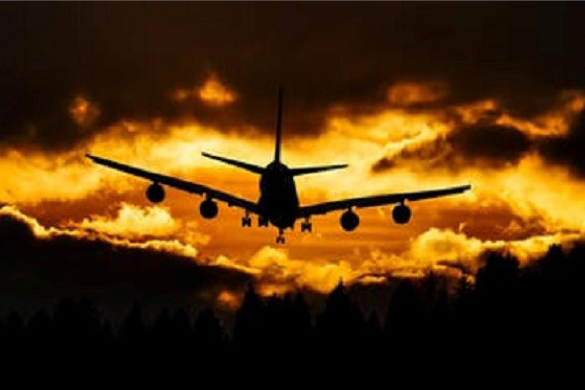 aeroplane flying into sunset