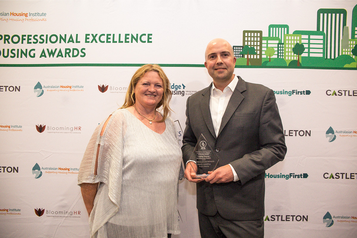 Woman and man holding affordable housing award
