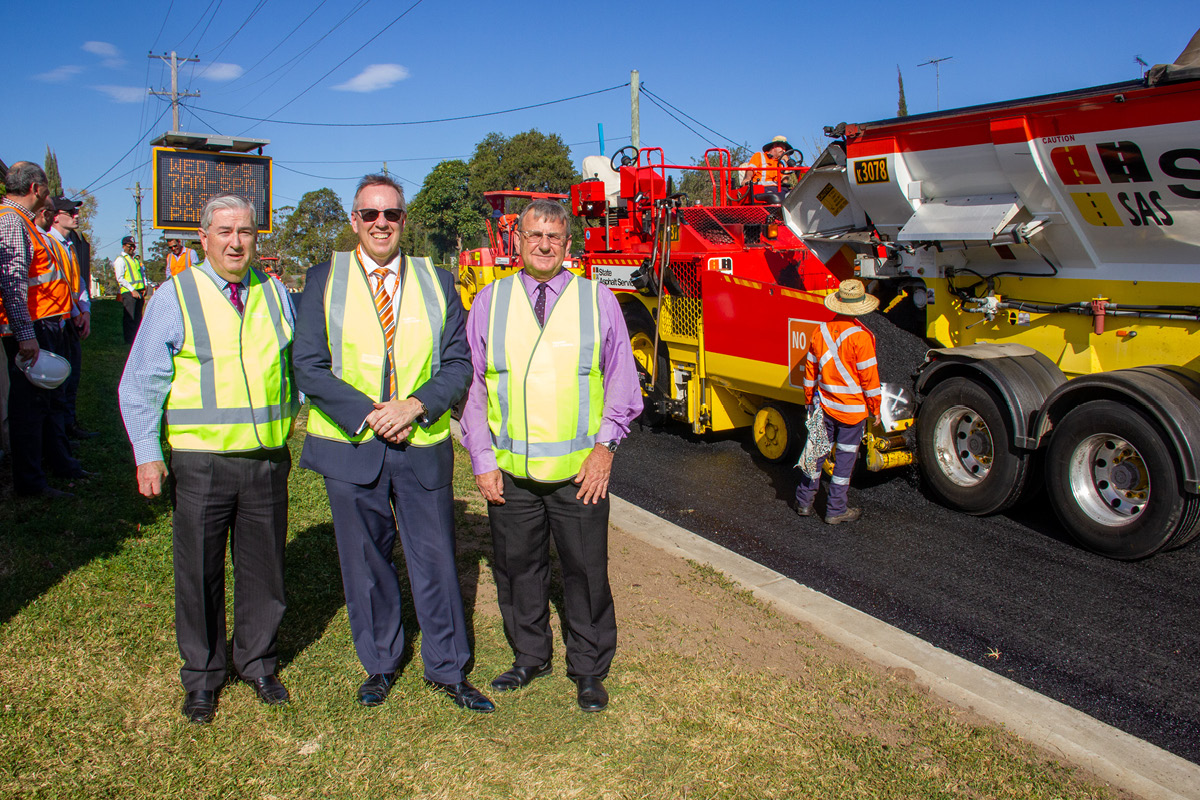 Mayor and council representatives watching as workmen lay new glassphalt road surface in Stafford Street Penrith
