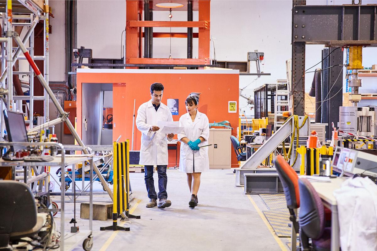 Man and woman walking through engineering facility