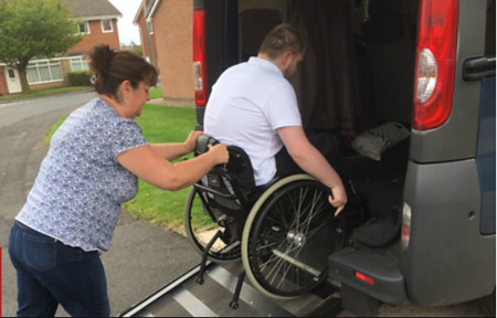 Wheelchair user being helped into transporter.