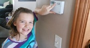 Girl pointing to thermostat adjustment to save energy