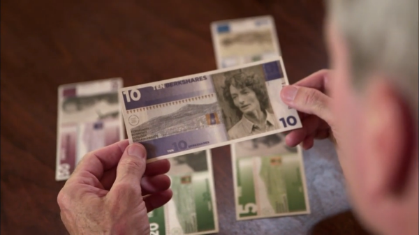 Henry Rollins holds up the 10 BerkShare note