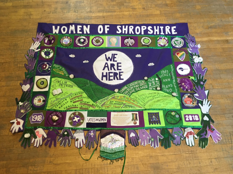 Image shows a rectangular textile banner in the colours purple green and white. The banner reads women of Shropshire along the top with the names of women sewn into the shapes of hills beneath a circle which reads we are here.