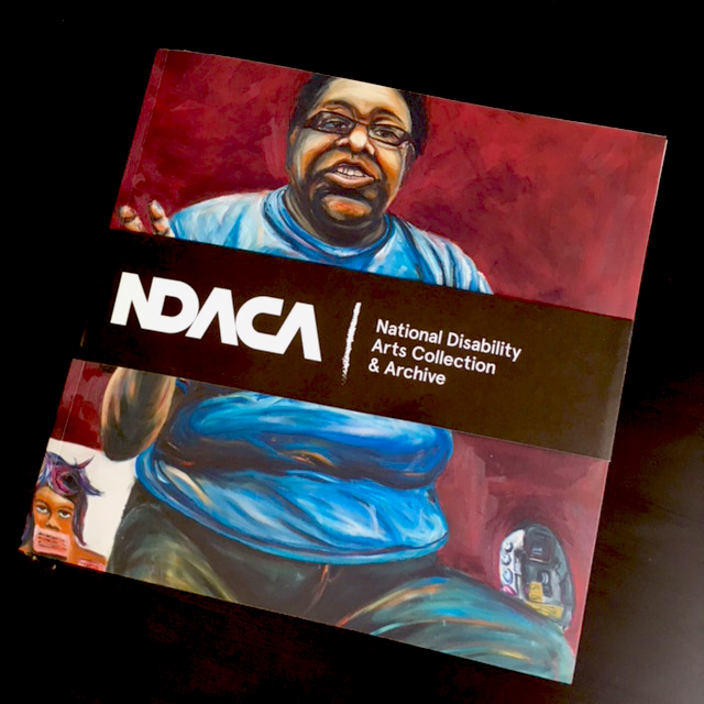 Image shows the NDACA brochure. On the cover is a painting of a person with short black hiar dark glasses, dark skin, wearing a blue tshirt and jeans. The image is obscured by a black horizontal band on which  NDACA National Disability Arts Collection and Archive is written in white.
