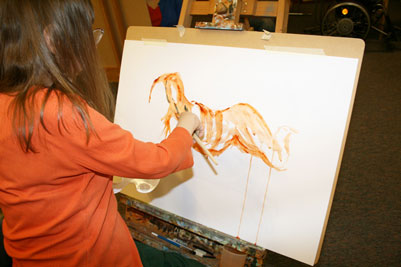 A person with long brown hair and an orange top paints a nude reclining figure on a piece of paper attached to a board, propped up on an easel.