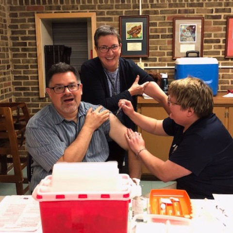 Rev. Eric getting flu shot with Rev. Marian in background ready to get one too