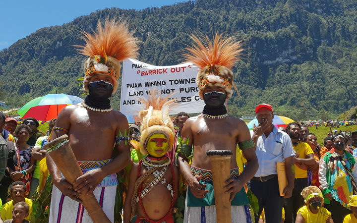 A child flanked my two men, all three in ceremonial mask and headdress with mountains and a crowd of protesters in the background