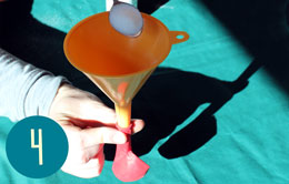 Spooning a white powder into a funnel placed in a baloon.