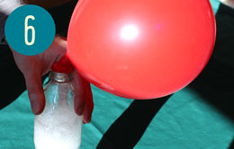 A red balloon, partially inflated on top of a bottle with fizzing liquid inside.