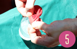 Stretching the mouth of a red balloon over the mouth of a bottle.