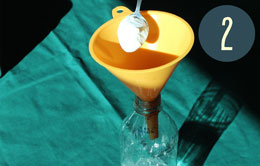 Spooning a white powder into a funnel placed in the top of a bottle.