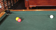 A red and a yellow ball touching. they point towards a pocket.