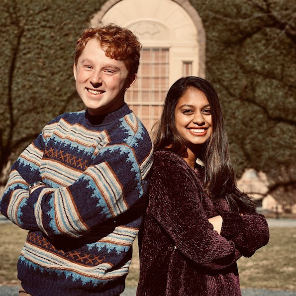 Two students posing back-to-back, smiling